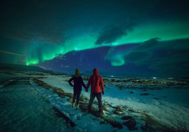 A couple holding hands in front of the Northern Lights