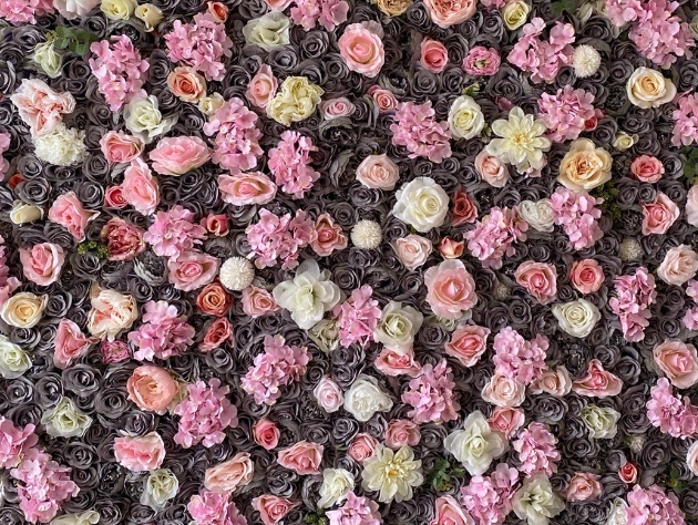 Close up of flower wall featuring grey roses and other blooms in pink, peach and lemon