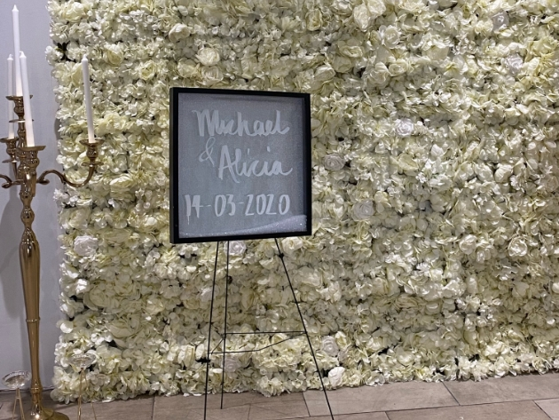 Flower wall in ivory with Michael & Alicia sign in the front and a tall gold candelabra