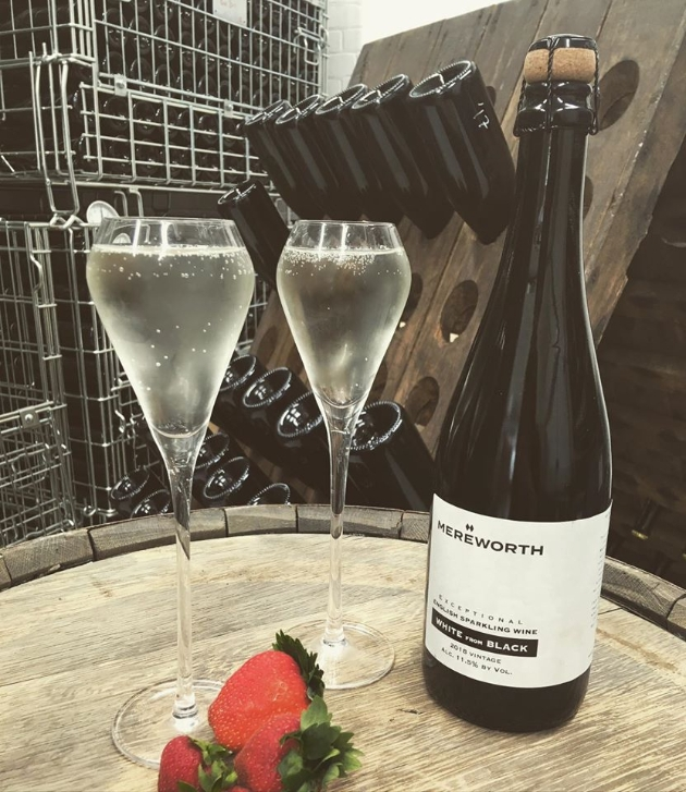 A bottle of Mereworth Wines' English sparkling wine, with two full champagne glasses and some strawberries