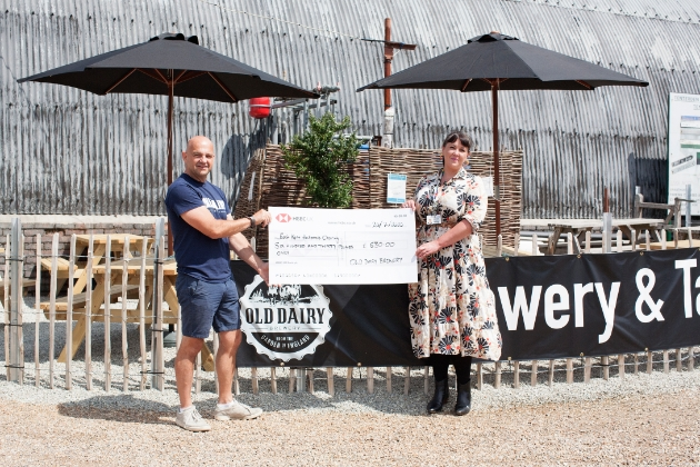 Old Dairy Brewery employee presenting a large cheque to East Kent Hospitals Charity representative