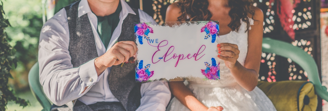 Bride and groom holding up we eloped sign