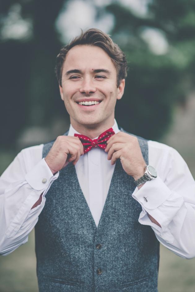 Groom straightening his red bow tie