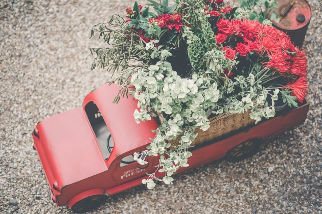 Red floral arrangement in the back of a red toy truck