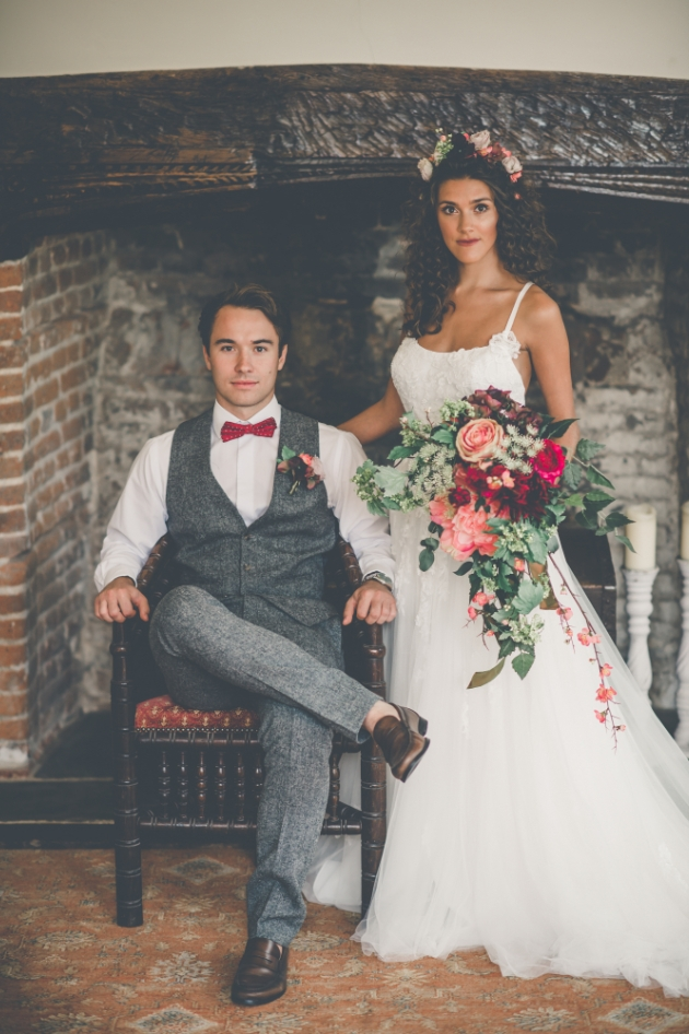 boho bride and groom in front of a fireplace at Westenhanger Castle