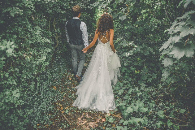 Bride and groom in the woods walking away from the camera