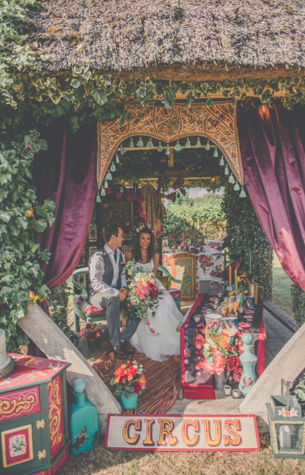 Bride and groom under cover of a gazebo surrounded by colourful quirky decor props