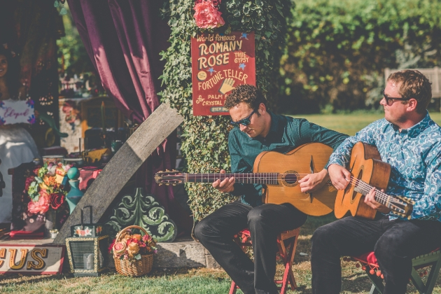 Two acoustic guitar players playing outside the wooden gazebo at Westenhanger Castle