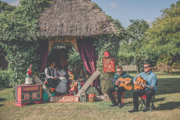 Two acoustic guitar players playing outside the wooden gazebo