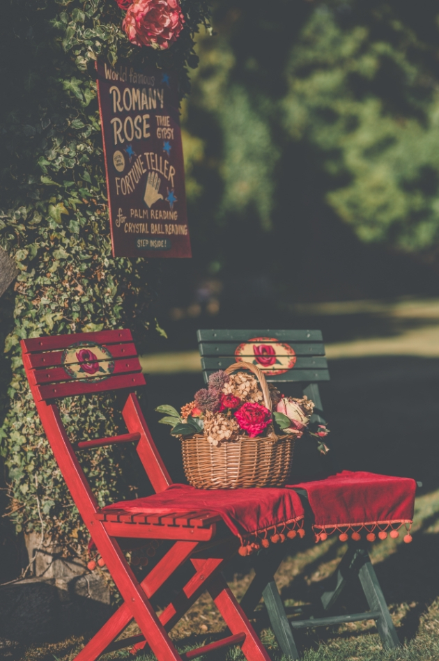 Red and green romany-style painted wooden chairs with a basket of flowers on them
