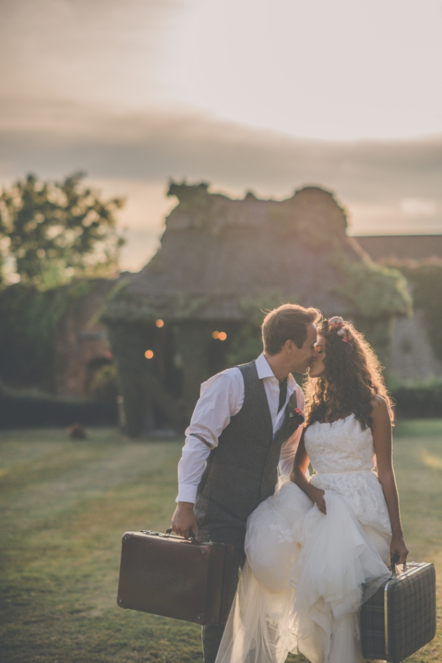 Bride and groom kissing suitcases in hand ready to elope