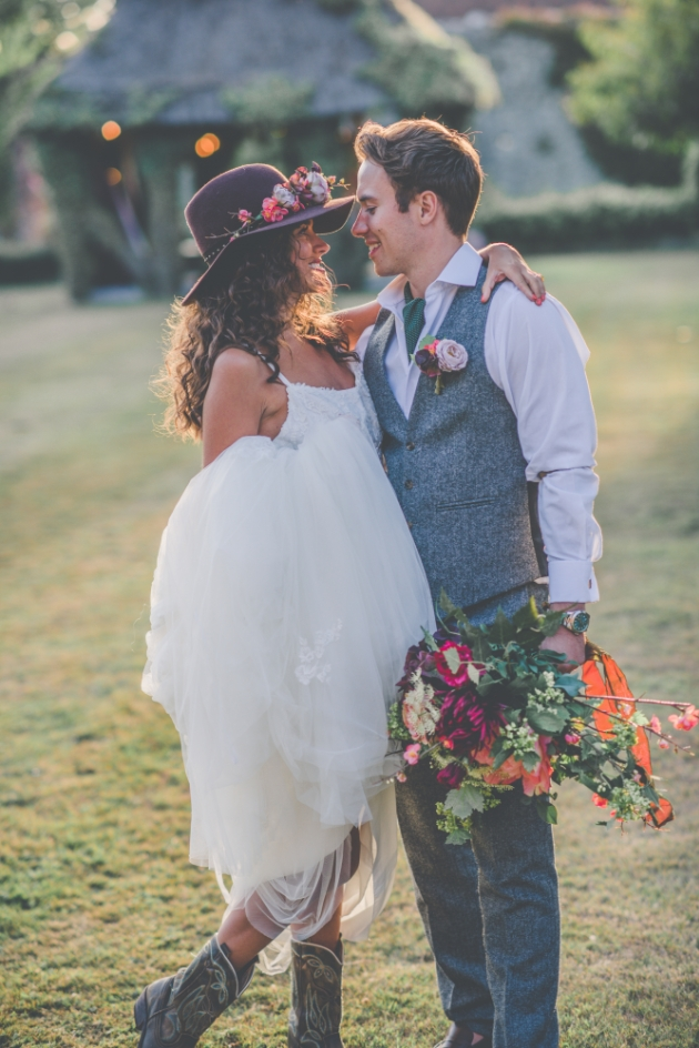 bride wearing boho hat and cowboy boots groom wearing green cravat and holding her bouquet