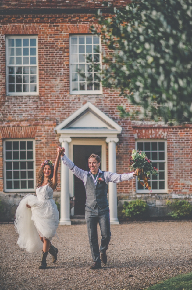 Bride and groom celebrating their elopement arms in the air