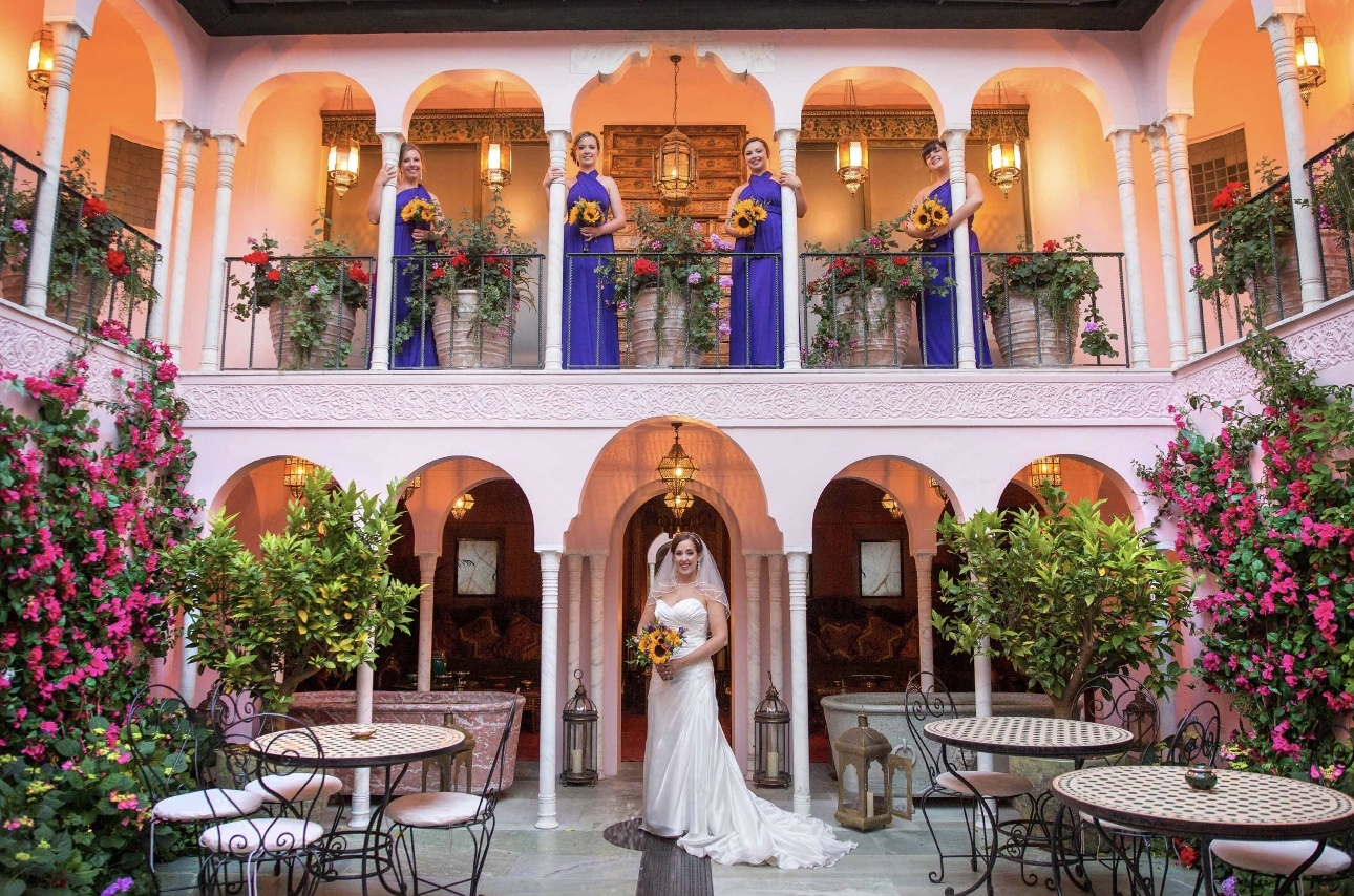 Bride and bridesmaids stand in archways
