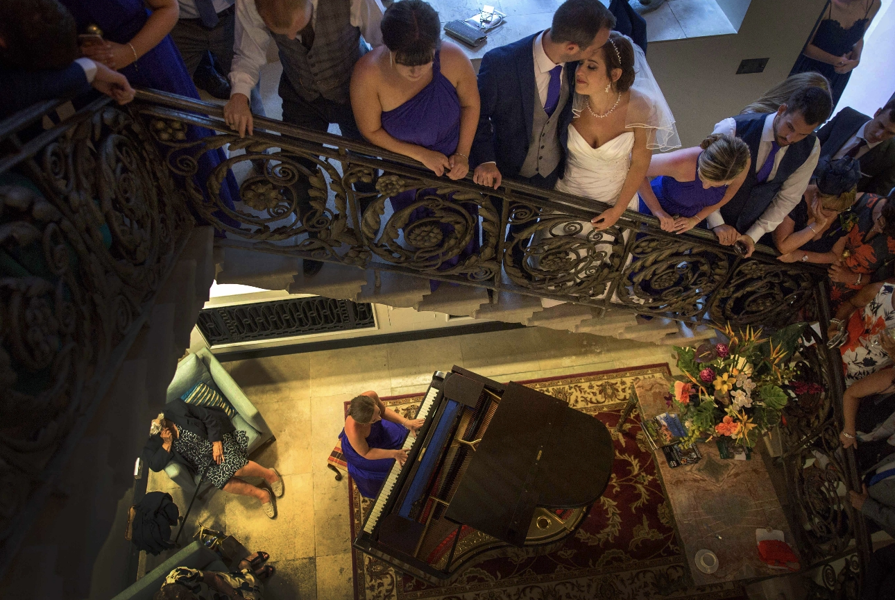 Bridal party on stairwell above pianist