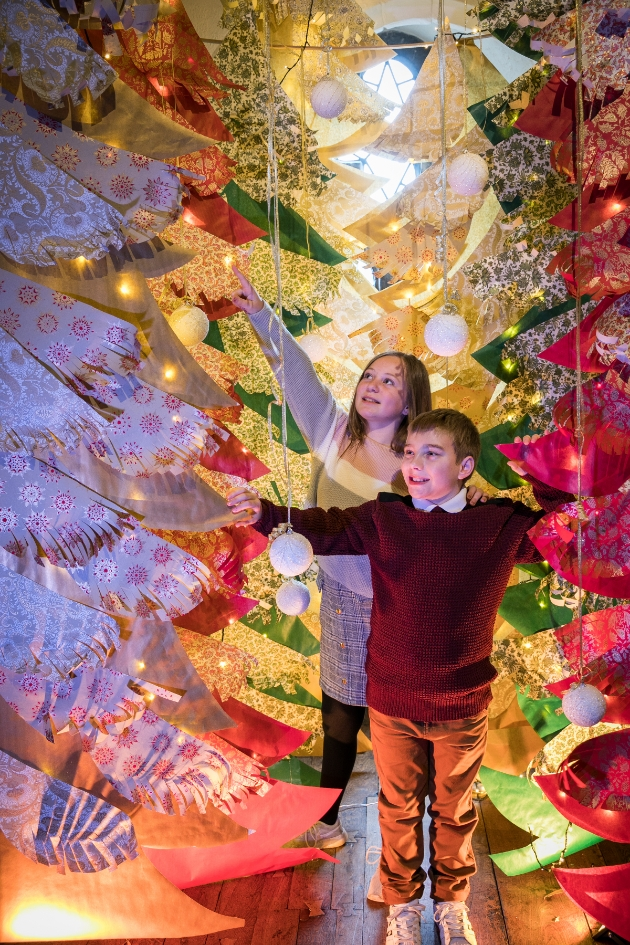 Boy and girl exploring a wonderland of wrapping paper Christmas trees at Leeds Castle