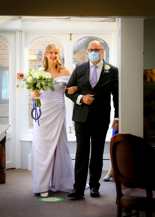 Bride walking down the aisle on her father's arm. Father is wearing a face mask