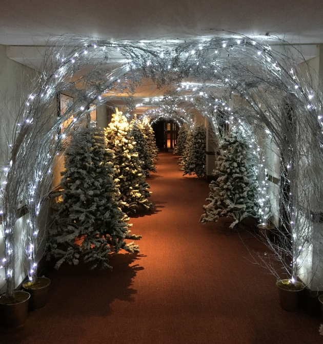 corridor decorated for Christmas with trees and lights like a winter wonderland