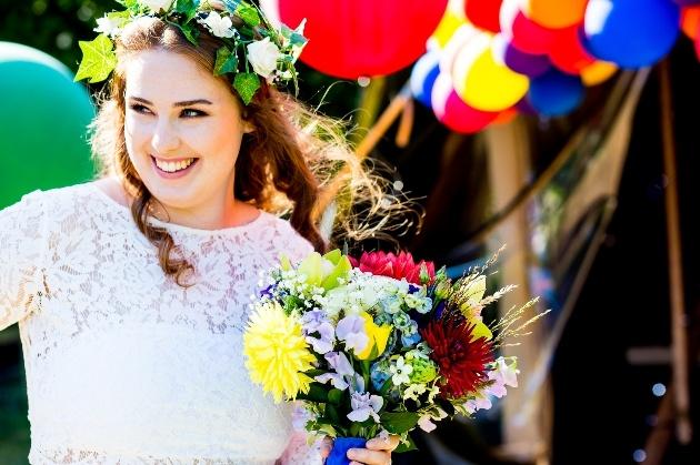 Smiling carefree boho bride against colourful balloon backdrop
