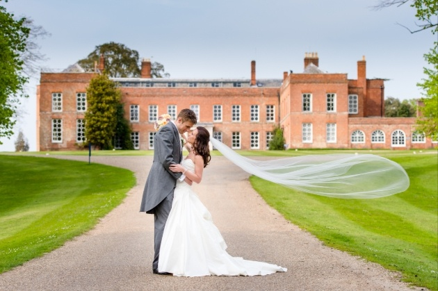 Bride and groom on the lawns in front of Braxted Park