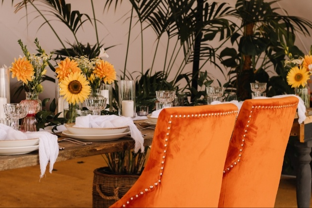 Wedding breakfast table with orange velvet chairs and sunflowers