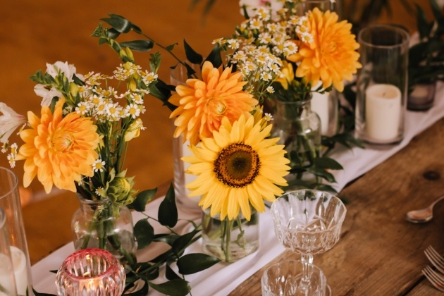 Central runner of wedding breakfast table with sunflowers and yellow blooms