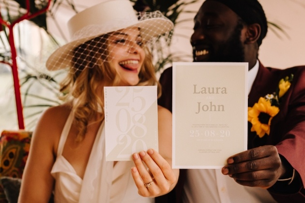 couple holding up their wedding stationery