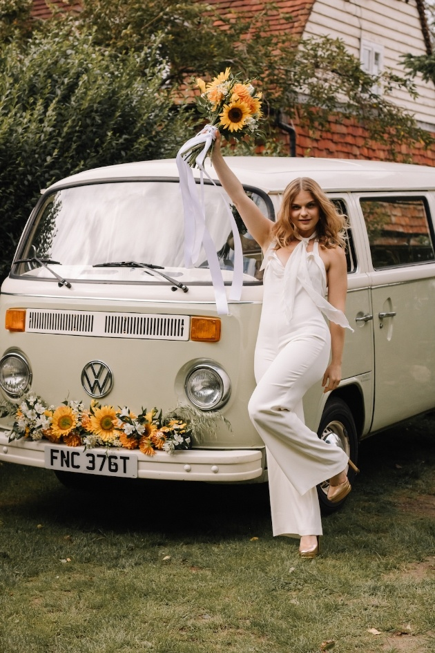 Bride dressed in wedding jumpsuit with sunflower bouquet in front of VW Camper