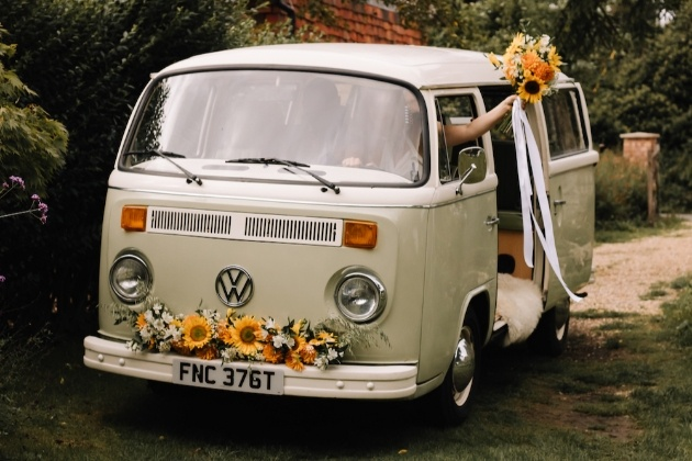 VW Camper with couple inside. Bride is waving her bouquet out of the window