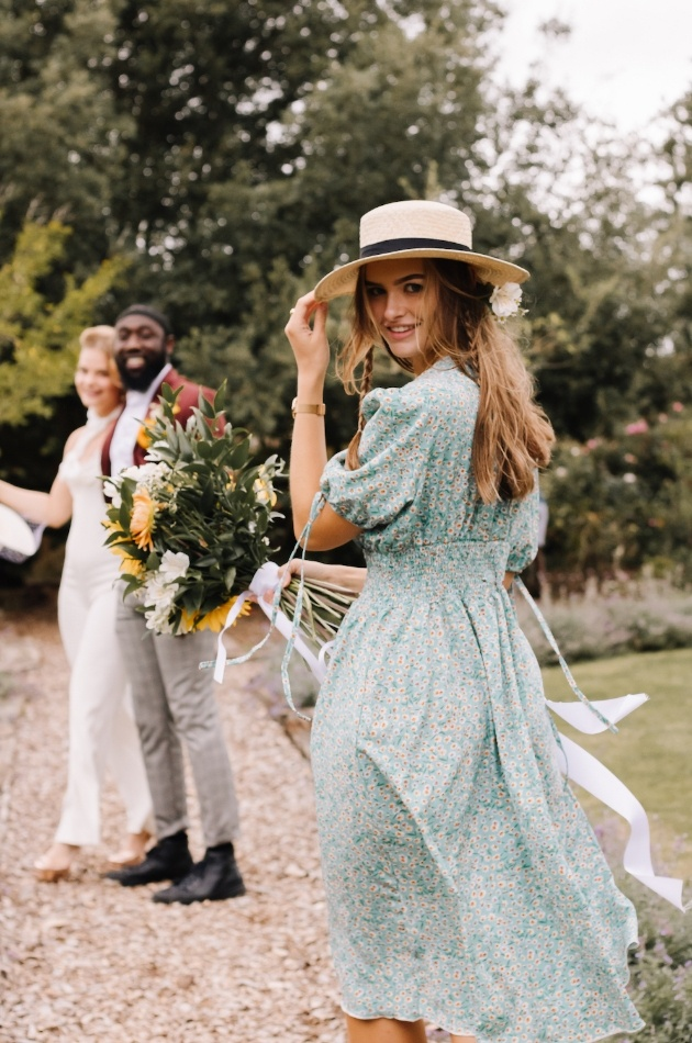 Bridesmaid caught in a breeze with straw boater, bouquet and couple in the background