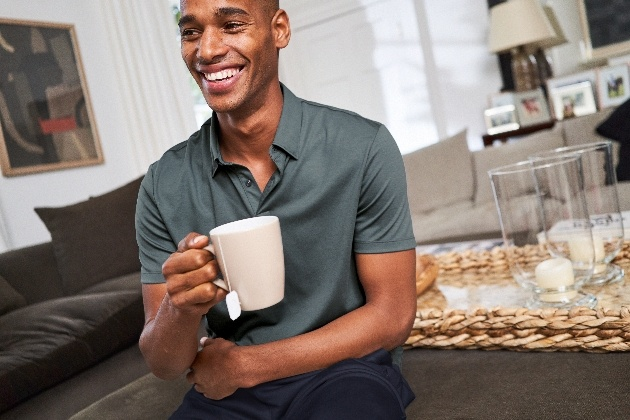 man in loungewear sitting at table with coffee