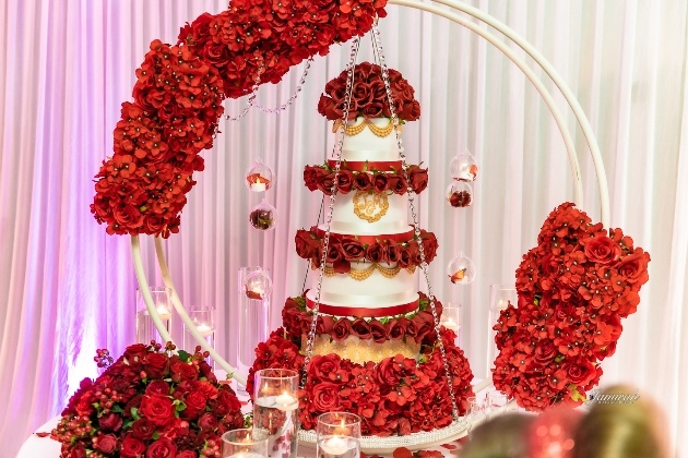 hanging cake decorated with gold initials and red roses