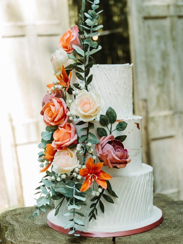 White textured three tier cake with peach and pink sugar flowers by iced Images cakes