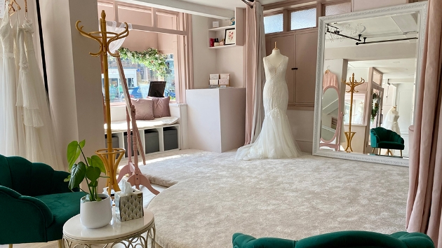 interior of Vicki's bridal boutique with emerald velvet chairs and large mirror