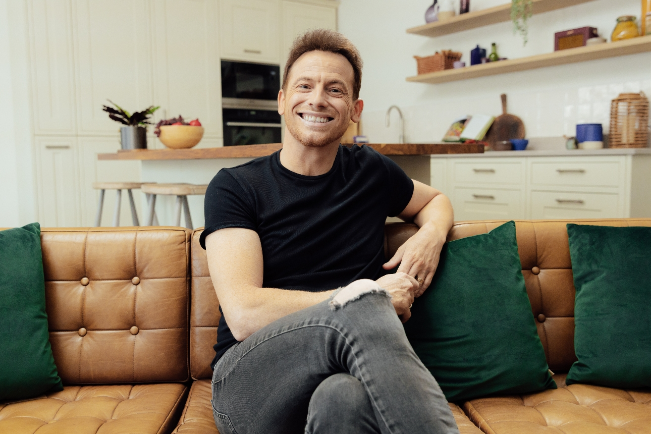 Joe Swash on a brown leather sofa in a kitchen