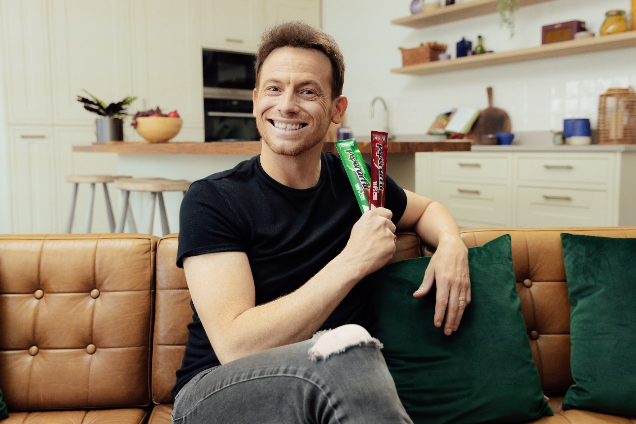 Joe on sofa holding two peperami