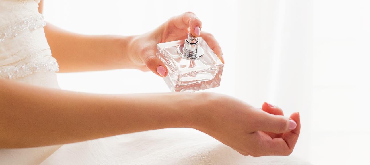 Bride spraying perfume on to her wrist