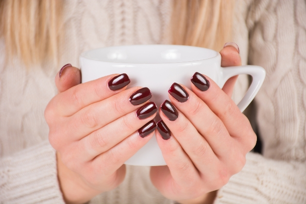 woman wearing dark nail polish for the winter cupping her hands around a mug of hot drink
