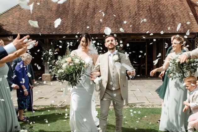bride and groom walking through a confetti shower